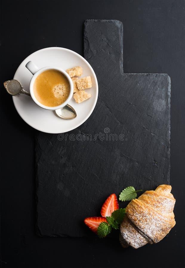 Den espressokaffekoppen och gifflet med nya jordgubbar på svart kritiserar stenbrädet över mörk bakgrund royaltyfri foto