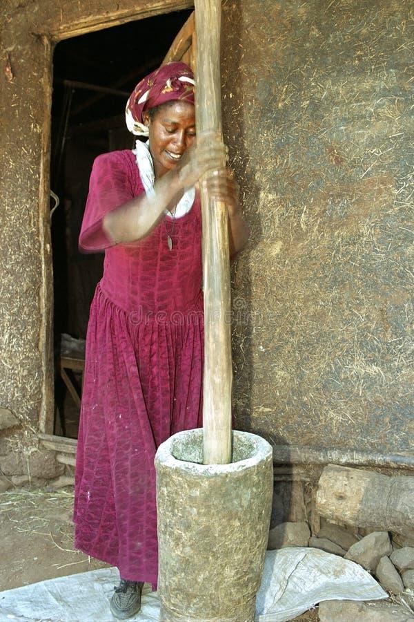 Den etiopiska kvinnan dunkar korn in i mjöl royaltyfri fotografi