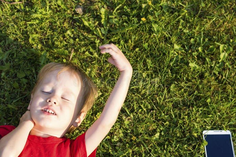 Den europeiska barnpojken ligger med hans ögon som stängs på gräset och, vilar Begreppet av utbildning och beroende på grejer in royaltyfri bild