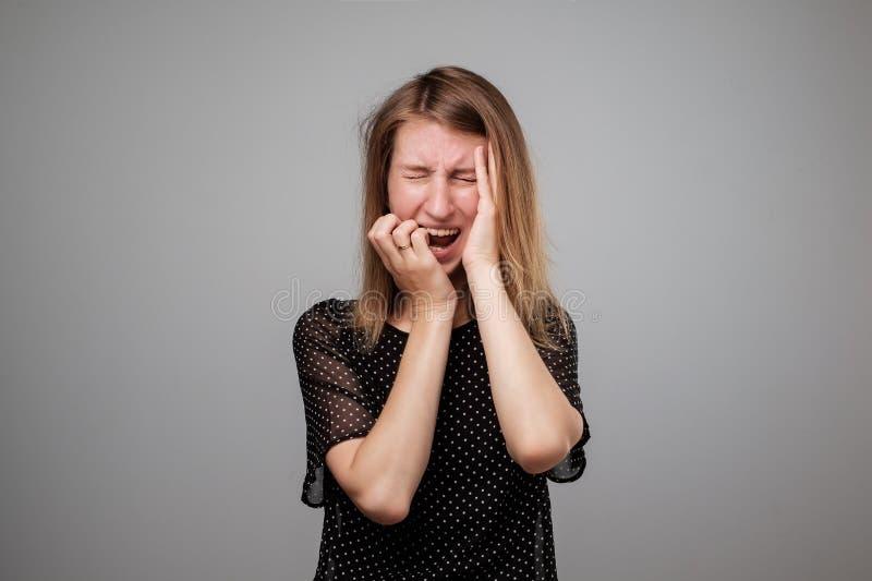 Den europeiska kvinnan i spänning går galen dra hennes hår i frustration royaltyfri foto