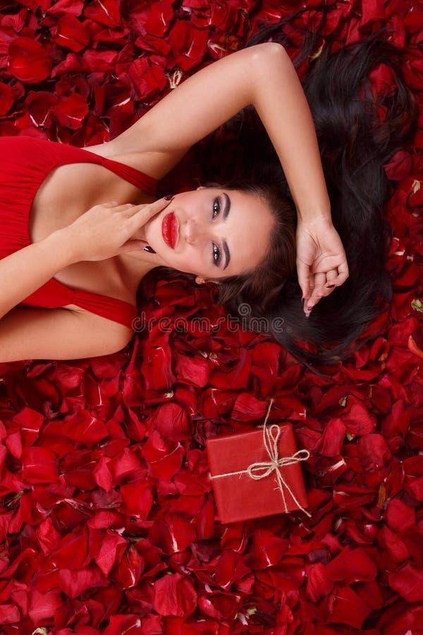 Den europeiska kvinnan ligger i rosa kronblad nära en gåvaask och hållhänder nära framsidan royaltyfri bild