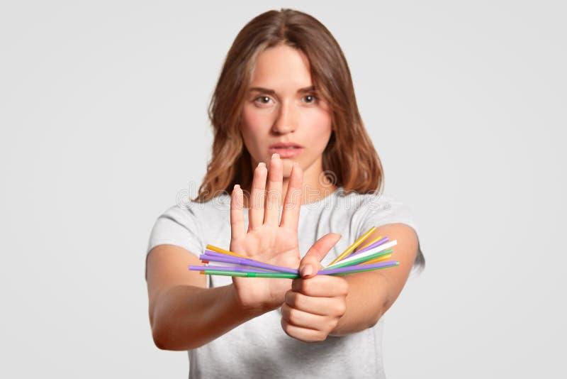 Den europeiska kvinnan med allvarligt uttryck, plast- sugrör för håll, säger inte till disponibla plast- dricka sugrör för metall royaltyfri bild