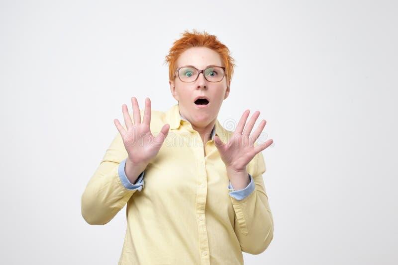 Den europeiska kvinnan med exponeringsglas som ser kameran som håller munsned boll, öppnade känslig chockat och stressat arkivfoton
