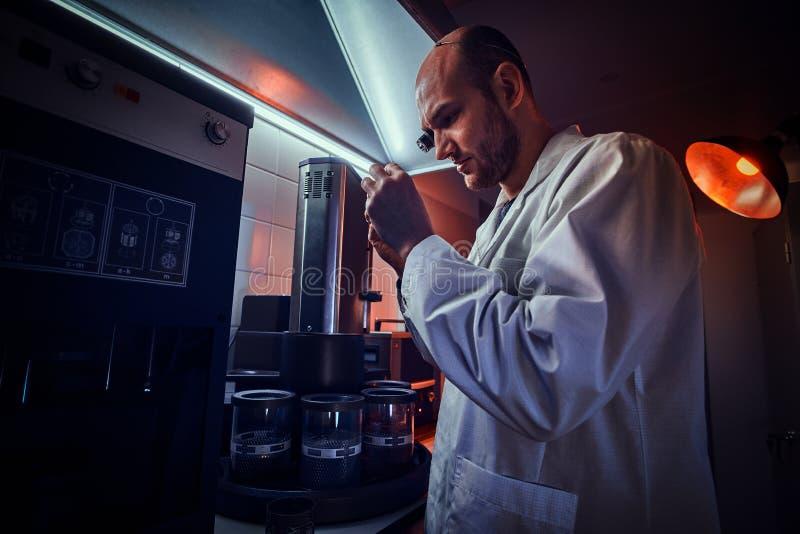 Den Expirienced urmakaren arbetar med autoclaven p? hans egen studio fotografering för bildbyråer