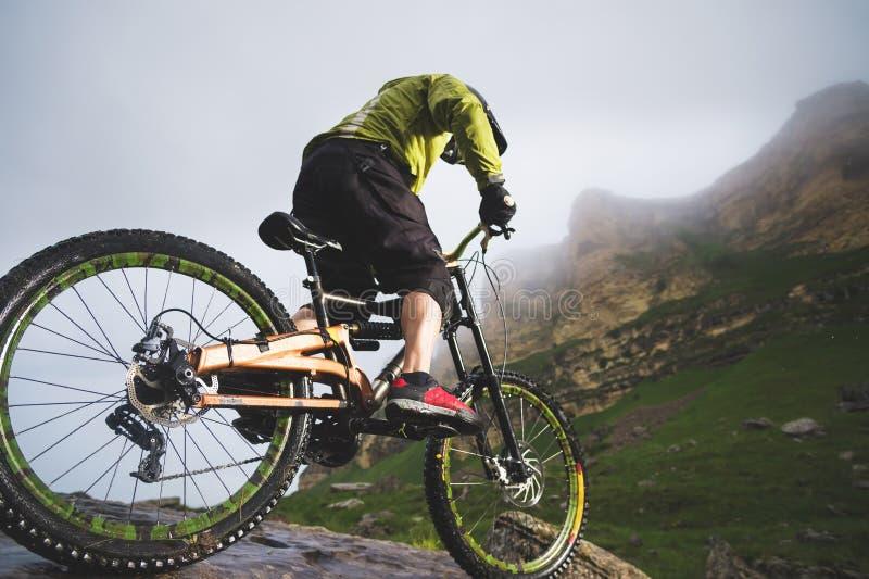Den extrema mannen för mountainbikesportidrottsman nen i hjälmridning mot en bakgrund av vaggar utomhus livsstil prov royaltyfria foton