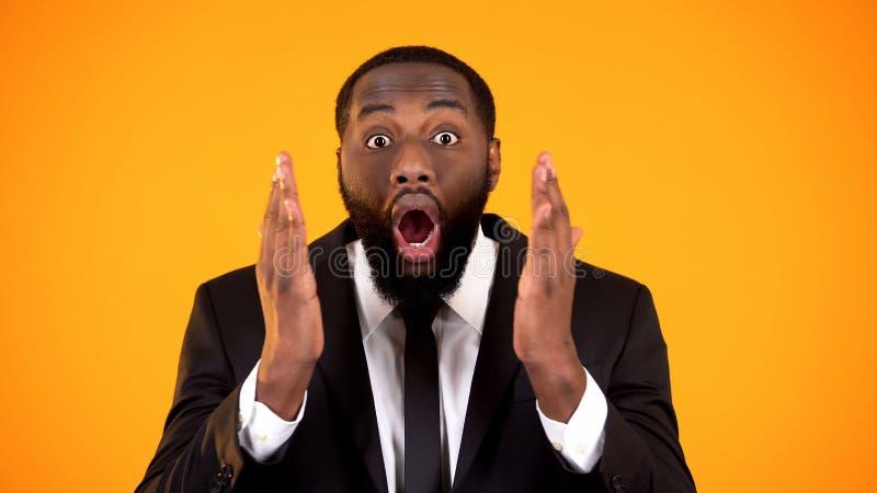 Den extremt f?rv?nade svarta mannen ?r dr?kten som ser till kammen, det attraktiva erbjudandet, f?rdelar fotografering för bildbyråer