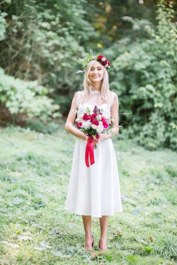 Den fängslande bruden med den röda bröllopbuketten står i gräset arkivbilder