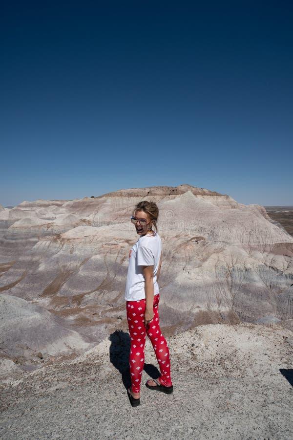 Den färdiga attraktiva aktiva kvinnan står och tycker om sikten på Blluen Mesa Trail i förstenade Forest National Park royaltyfri foto