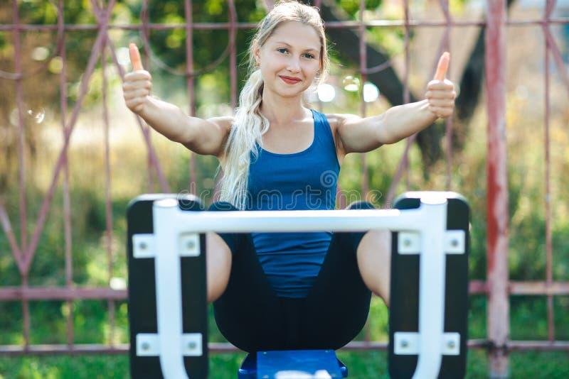 Den färdiga flickan i en blå skjorta och damasker i en parkeraidrottshall visar tummen som ser kameran och att le royaltyfria bilder