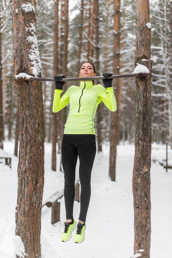 Den färdiga kvinnaidrottsman nen som utför handtag, ups i en stång Genomkörare för utbildning för vintergata utomhus- royaltyfri bild