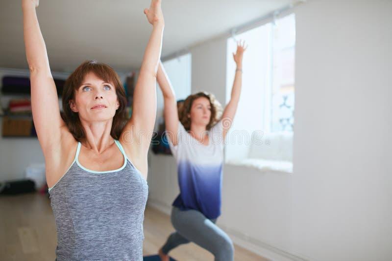 Den färdiga kvinnan i en meditativ yoga poserar på idrottshallen arkivfoton