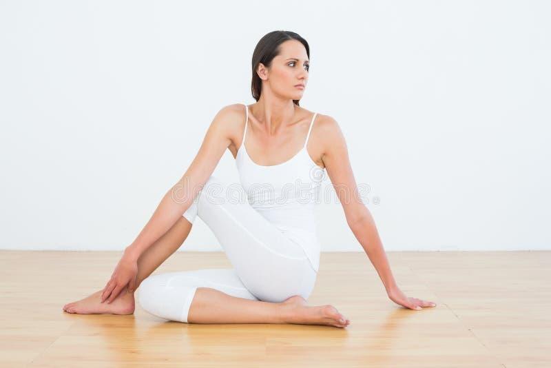 Den färdiga kvinnan som gör den halva ryggrads- vridningen, poserar i konditionstudio royaltyfri foto