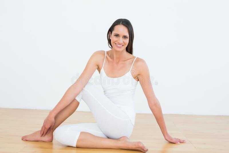 Den färdiga kvinnan som gör den halva ryggrads- vridningen, poserar i konditionstudio arkivfoto