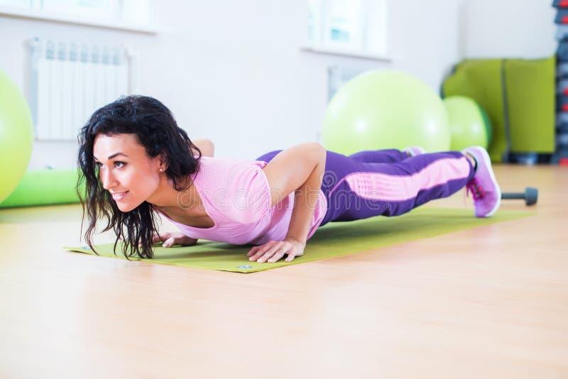 Den färdiga kvinnan som gör plankaövning och, skjuter ups arbete på triceps för buk- muskler arkivbild