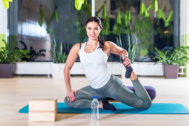 Den färdiga kvinnan som gör sträcka pilates, övar i konditionstudio royaltyfri bild