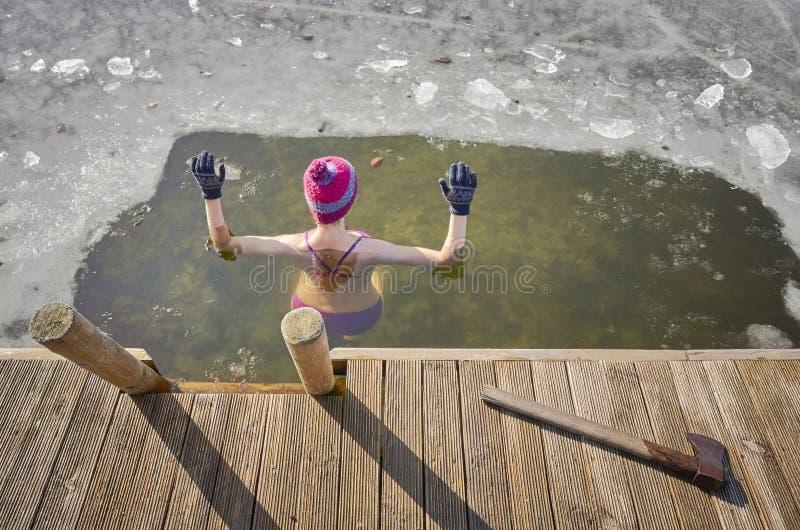 Den färdiga kvinnan utför isbad i ishålet royaltyfri foto