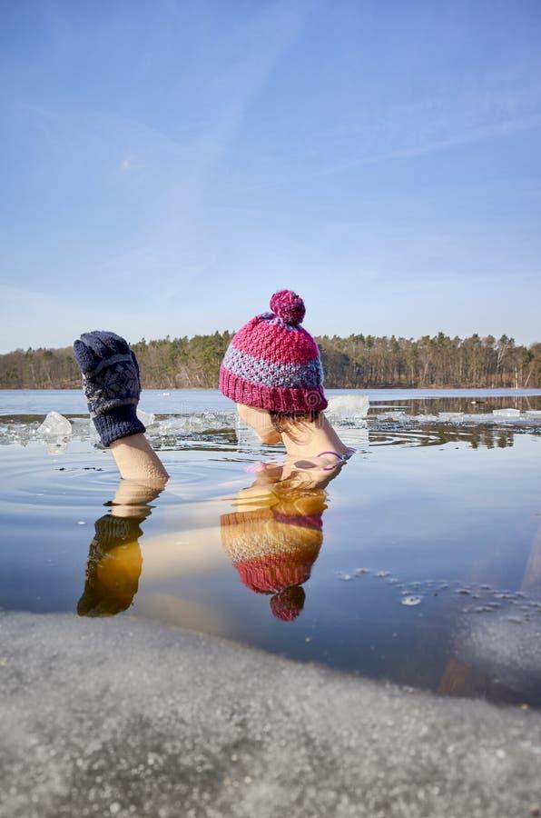 Den färdiga kvinnan utför isbad i ishålet arkivbilder