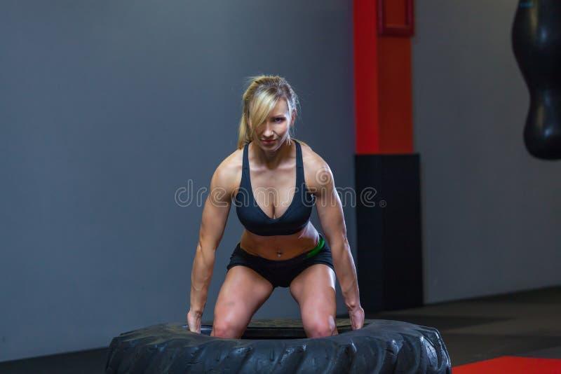 Den färdiga kvinnliga idrottsman nen som utarbetar med ett enormt gummihjul och att vända och, bär in idrottshallen Crossfit kvin arkivbild
