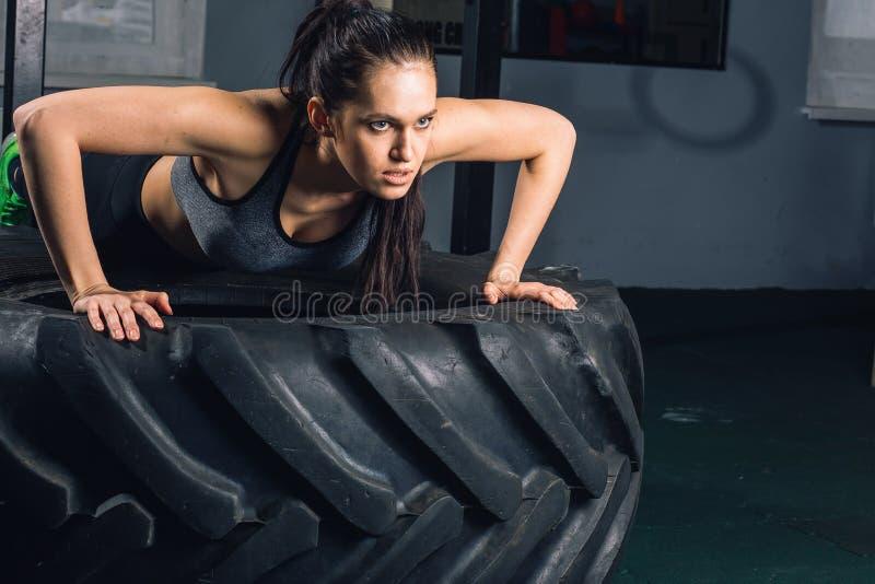 Den färdiga sportiga kvinnan som att göra skjuter, ups på begrepp för utbildning för gummihjulstyrkamakt arkivbilder