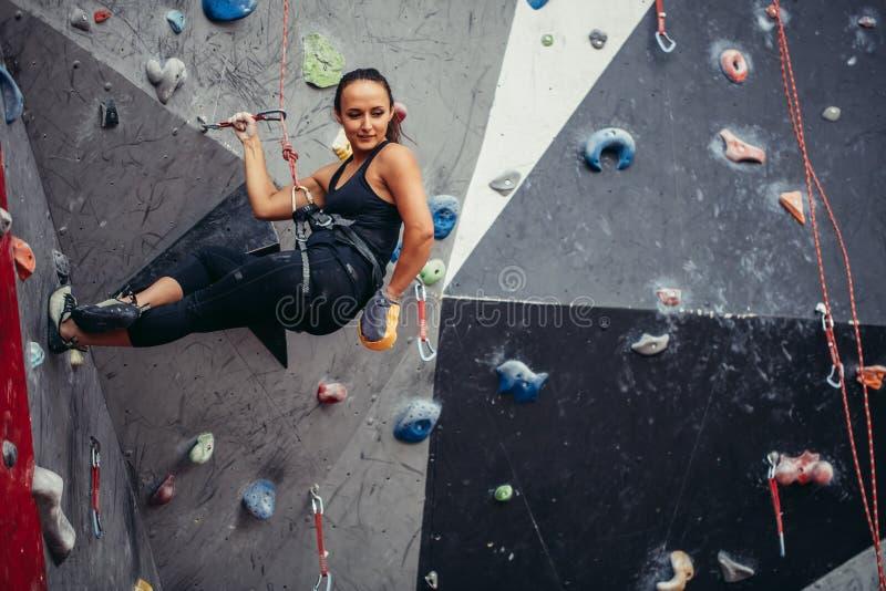 Den färdiga sportiga studentflickan som är rörande på, vaggar upp klättringväggen på idrottshallen arkivfoton