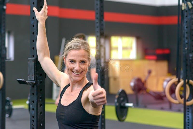 Den färdiga sunda kvinnan i en idrottshall ger upp tummar royaltyfri foto