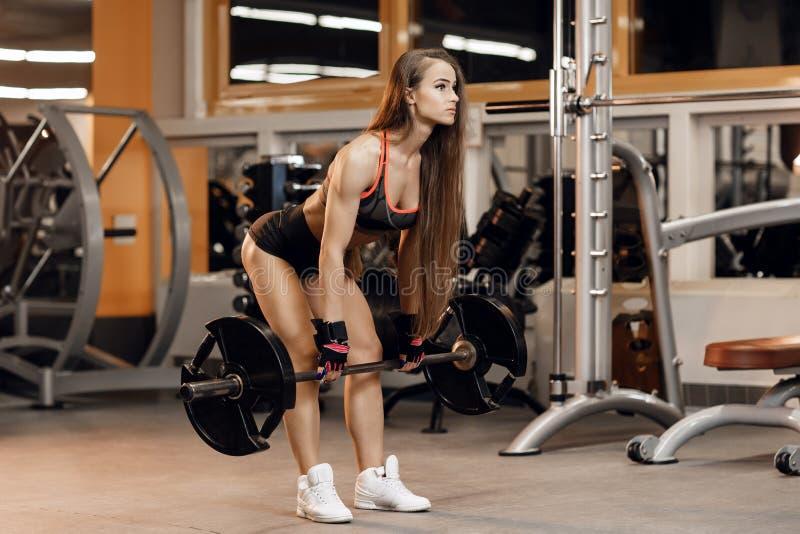 Den färdiga unga kvinnan gör deadlift att öva med skivstången i idrottshall Sport, kondition, powerlifting och folkbegrepp royaltyfria bilder