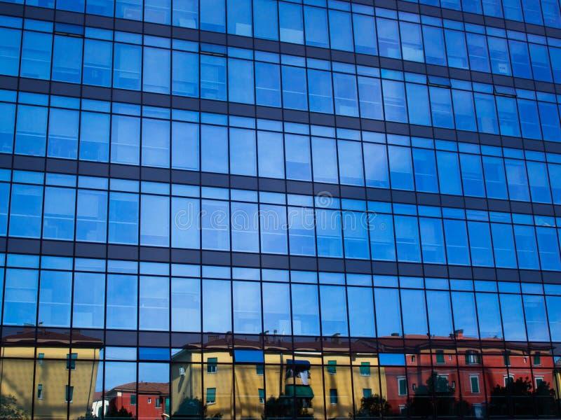 Den färgade lilla staden inhyser att reflektera på en stor spegelförsedd företags byggnad med blå himmel som bakgrund royaltyfria foton