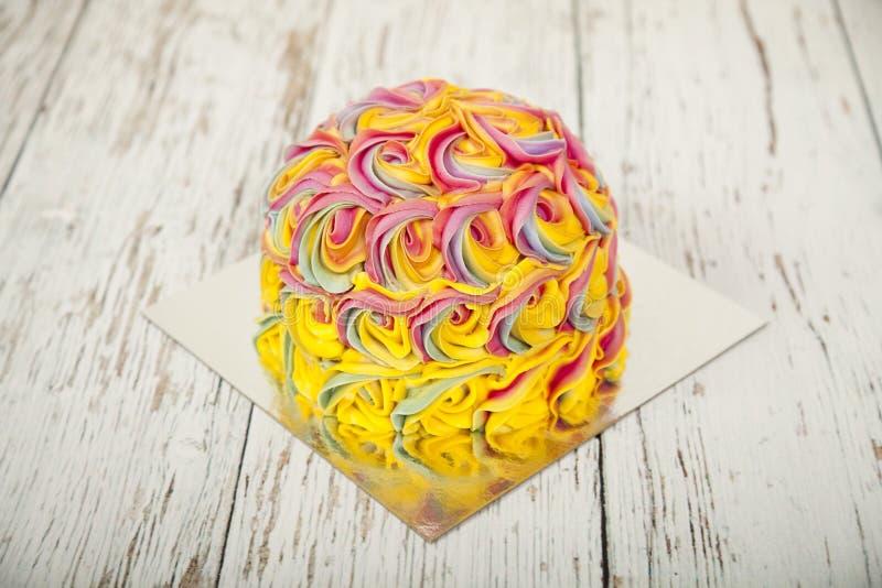 Den färgglade födelsedagkakan som är dold med isläggning, virvlar runt på en vit trätabell royaltyfri bild