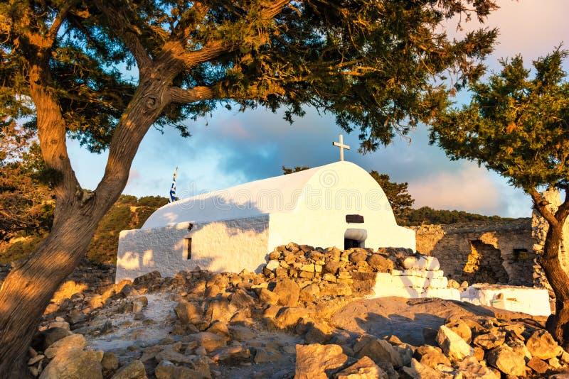 Den färgglade sikten av den grekiska ortodoxa kyrkan som byggs på, fördärvar av den Monolithos slotten under solnedgången Rhodes, arkivbild