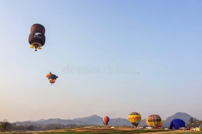 Den färgrika ballongen för varm luft som svävar över äng med berget, och blå himmel på Singha parkerar Chiang Rai International B arkivbilder