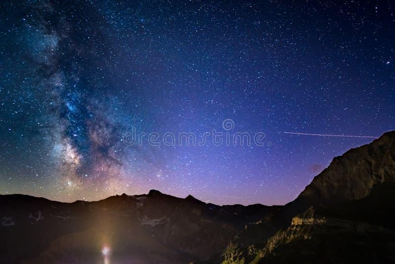 Den färgrika glödande Vintergatanbågen och den stjärnklara himlen från höjdpunkt upp på fjällängarna royaltyfri foto