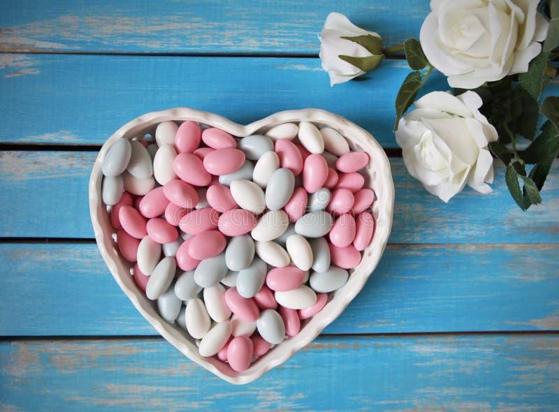Den färgrika godisen i vit hjärta formade bunken och vita rosor på trätabellen fotografering för bildbyråer