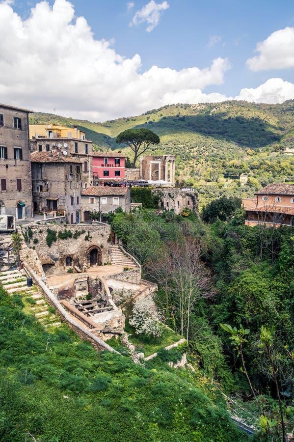 Den färgrika groteska gamla byn med roman fördärvar och kullar på ett moln fotografering för bildbyråer