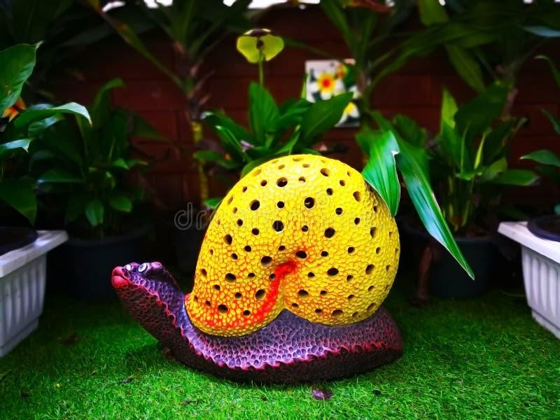 Den färgrika keramiska snigeln med det gula skalet och lilor förkroppsligar, wh fotografering för bildbyråer