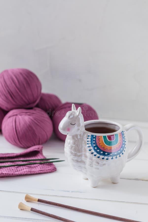 Den färgrika laman formade te, eller kaffe rånar med stickor, sax och ullgarn royaltyfri foto