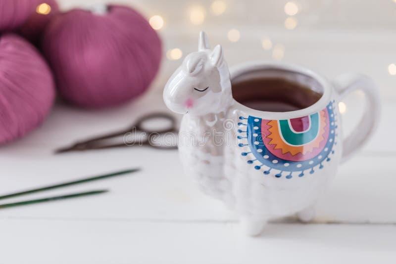 Den färgrika laman formade te, eller kaffe rånar med stickor, sax och ullgarn arkivfoto