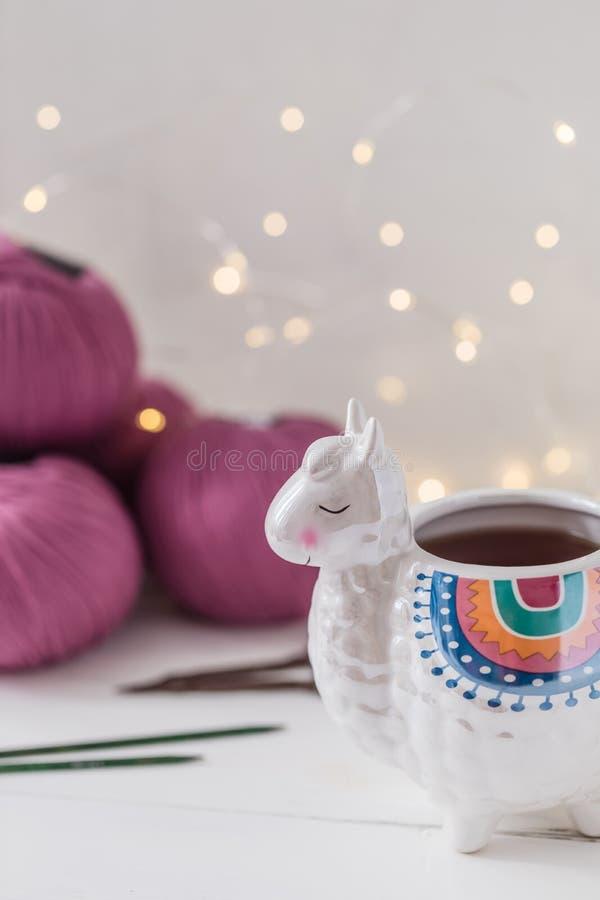 Den färgrika laman formade te, eller kaffe rånar med stickor, sax och ullgarn royaltyfria bilder
