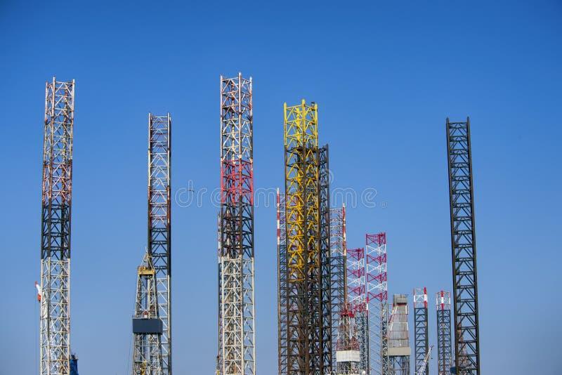 Den färgrika oljeplattformen lägger benen på ryggen högt övre, över hela och himmelblått arkivfoto