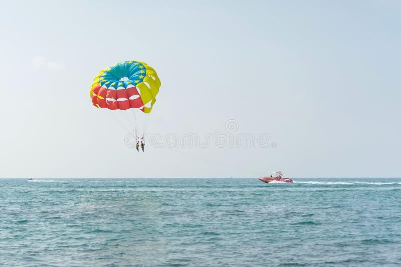 Den färgrika parasailvingen drog vid ett fartyg i havsvattnet - Alanya, Turkiet royaltyfri bild