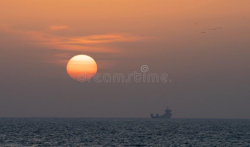Den färgrika solnedgången i havet, är ett lastfartyg royaltyfria foton