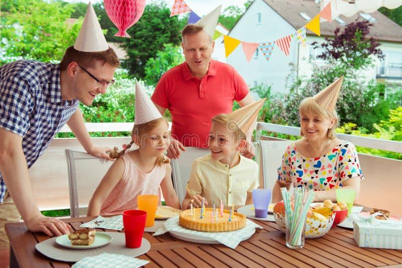 Den färgrika ståenden av den lyckliga familjen firar födelsedag och morfadern royaltyfria bilder