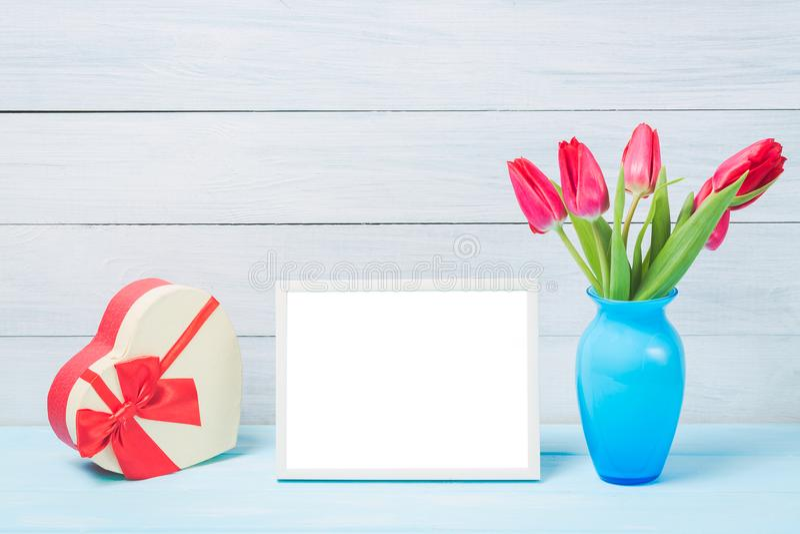 Den färgrika tulpan för den röda våren blommar i trevlig blå vas- och mellanrumsfotoram med dekorativ hjärtagiftbox på ljus träba arkivfoton