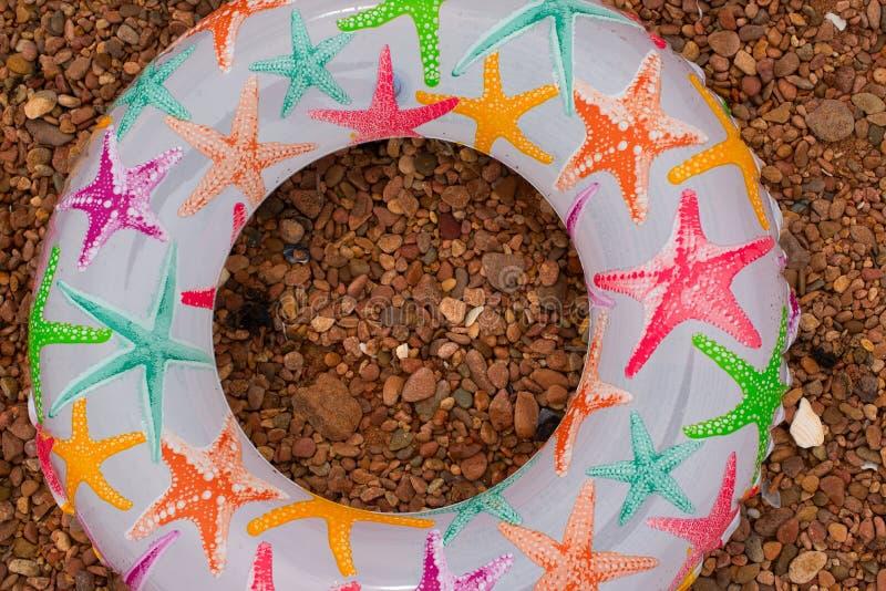 Den färgrika uppblåsbar behandla som ett barn cirkellögner på kusten royaltyfri fotografi