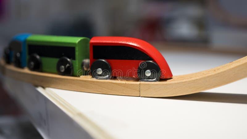 Den färgstarka leksakståget är på träspåret arkivfoton