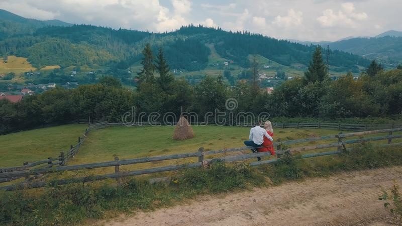 Den f?r?lskade mannen och kvinnan sitter p? staketet n?ra byn i bergen arkivbilder