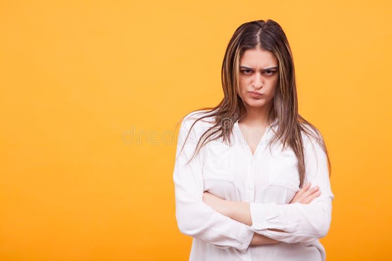 Den förargade unga kvinnan klädde casualy anseende över gul bakgrund royaltyfria bilder