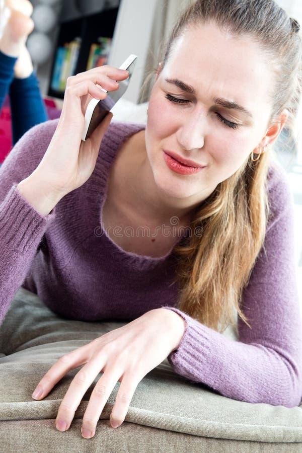 Den förargade unga kvinnan smärtar in innehavtelefonen långt från öron arkivbild