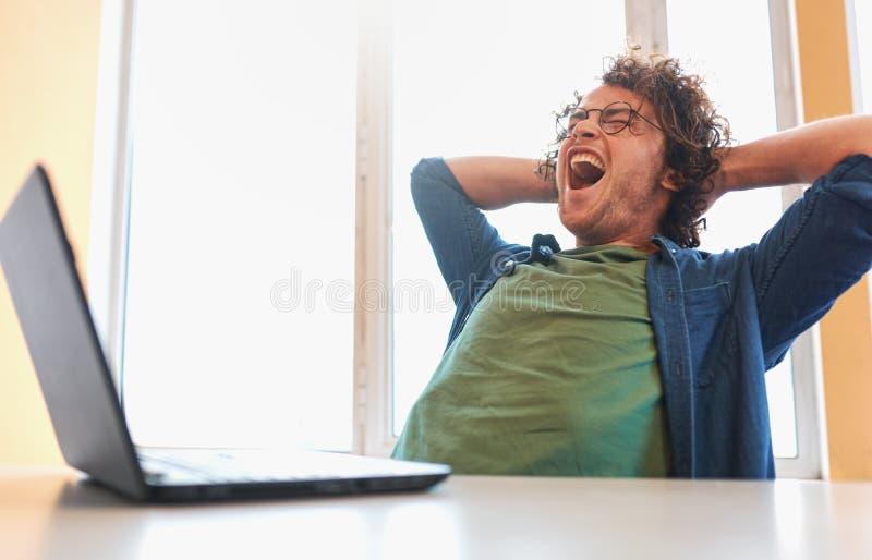 Den förargade unga mannen med lockigt hår som sitter på hans skrivbord med bärbar datorkänsla, förargar arkivfoto
