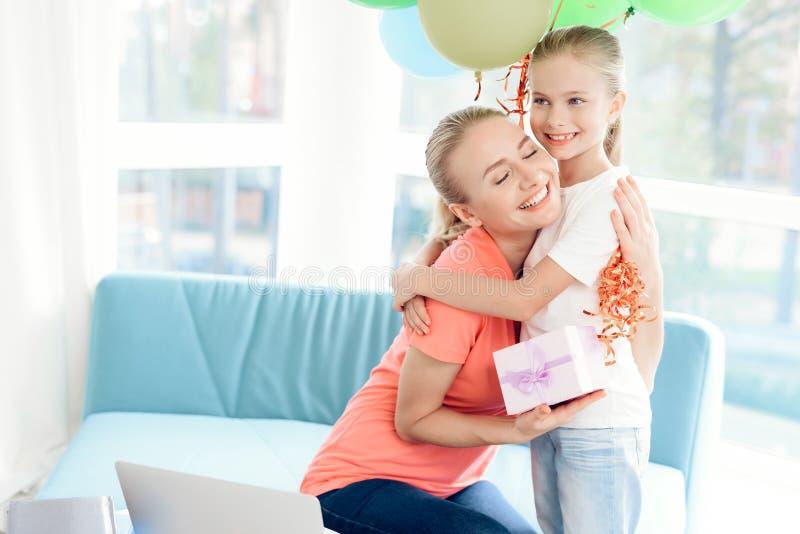 Den förberedda flickan en överraskning för hennes moder Förberedd gåva för liten flicka för mamma Hon rymmer ballonger royaltyfria foton