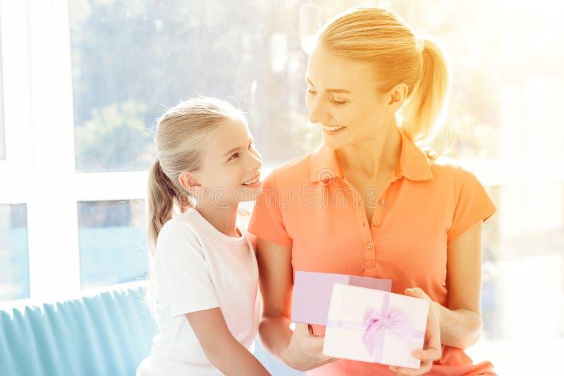 Den förberedda flickan en överraskning för hennes moder Förberedd liten flicka en gåva för mamma arkivfoton